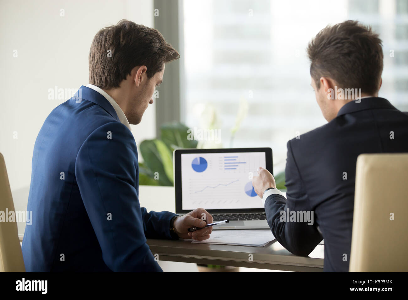 Two CEO analyzing financial rates on laptop screen - Stock Image