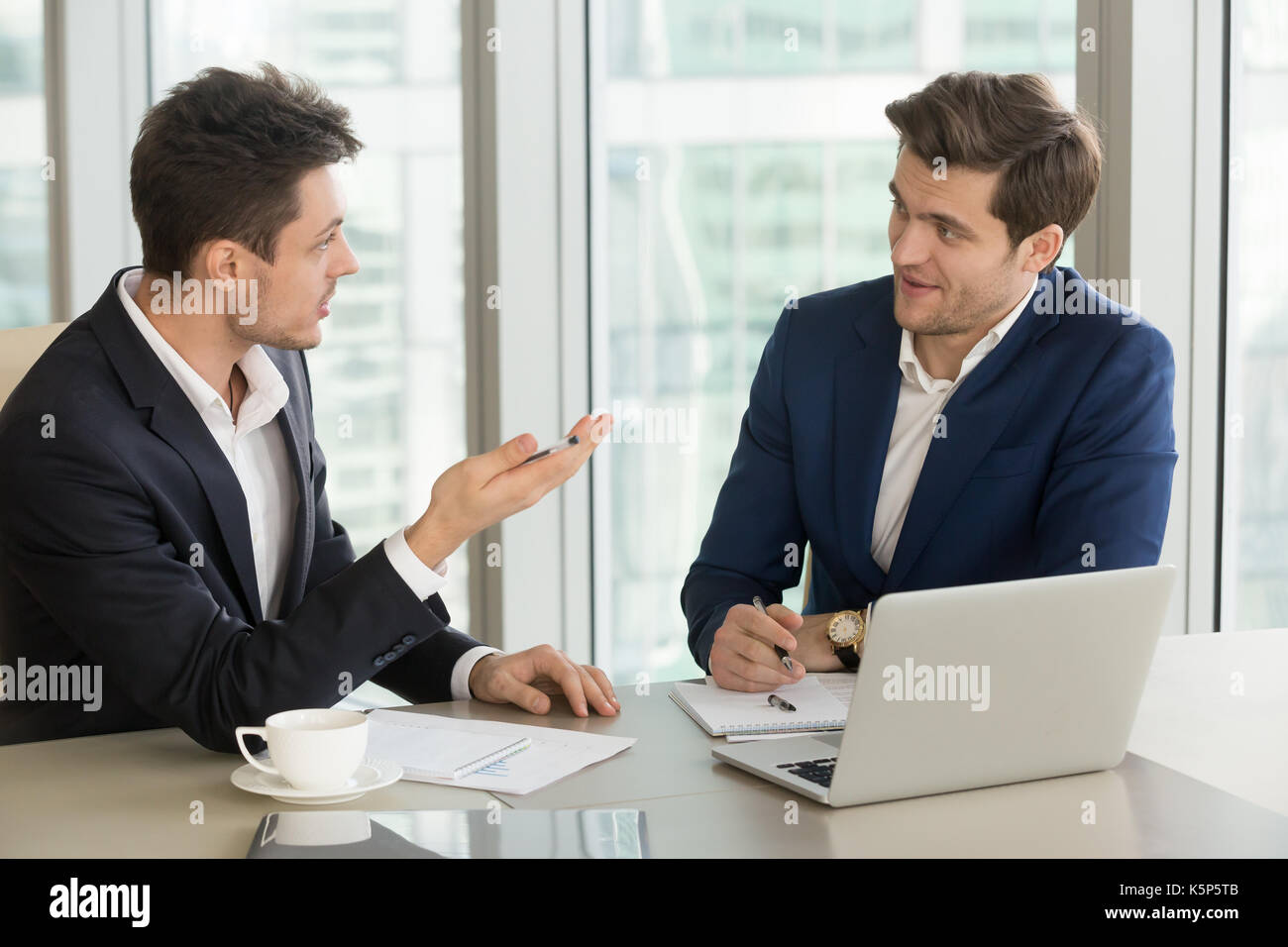 Young businessman convincing experienced colleague - Stock Image