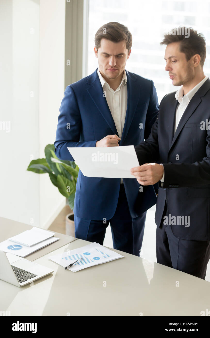 Entrepreneurs discussing company financial results - Stock Image