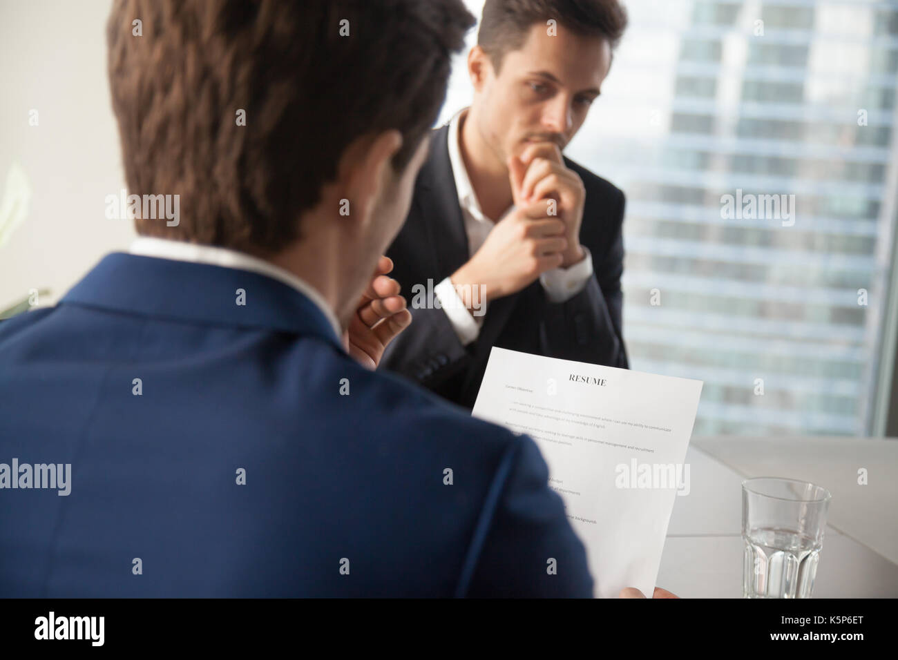 Hiring manager reading job candidates resume - Stock Image