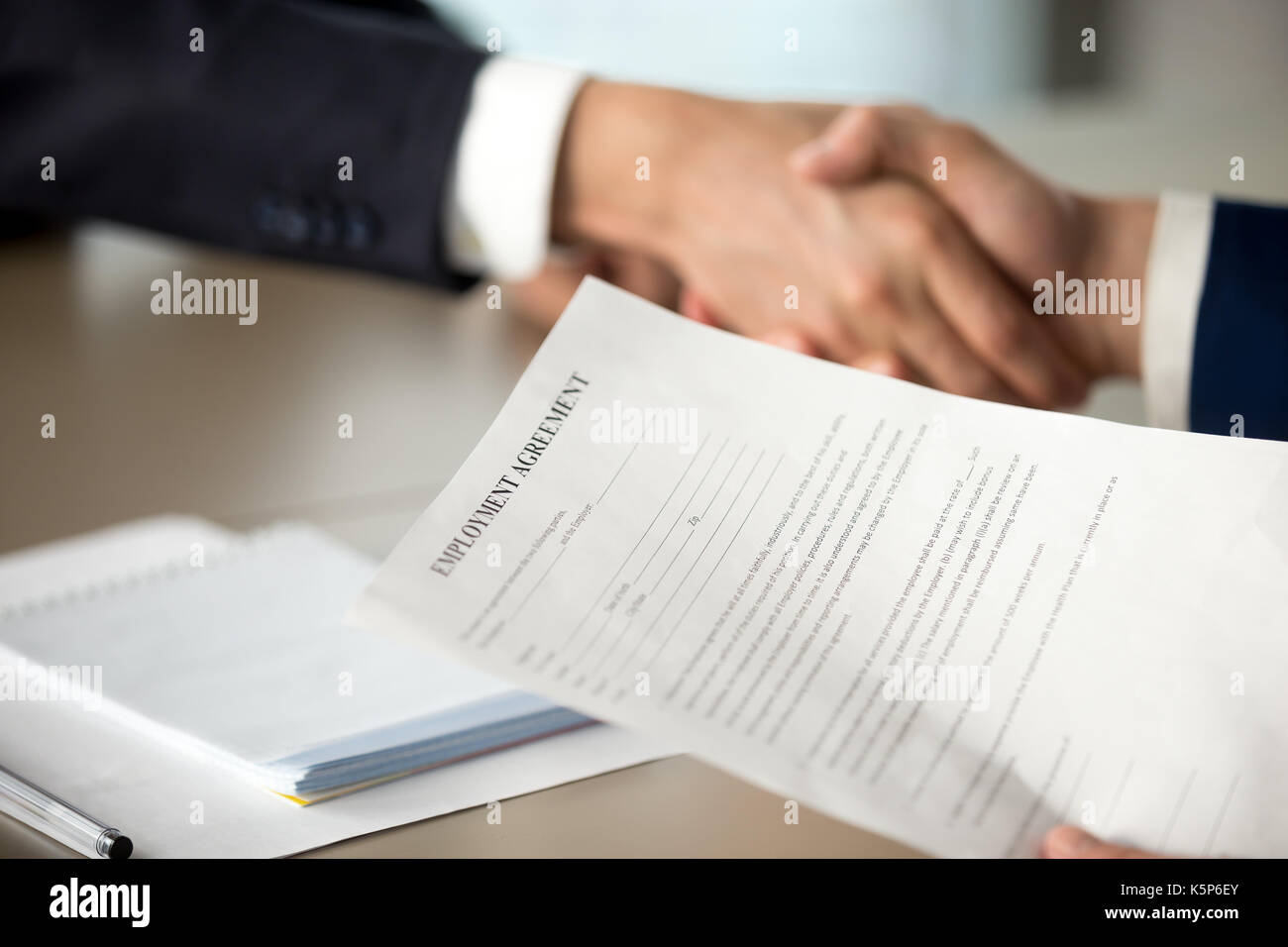 Boss handshaking and offering employment agreement - Stock Image