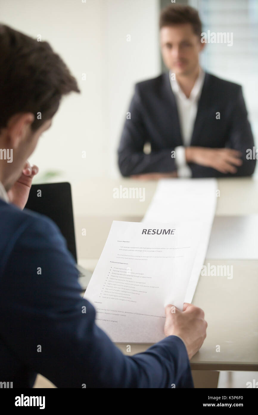Interviewer reading applicants long resume - Stock Image