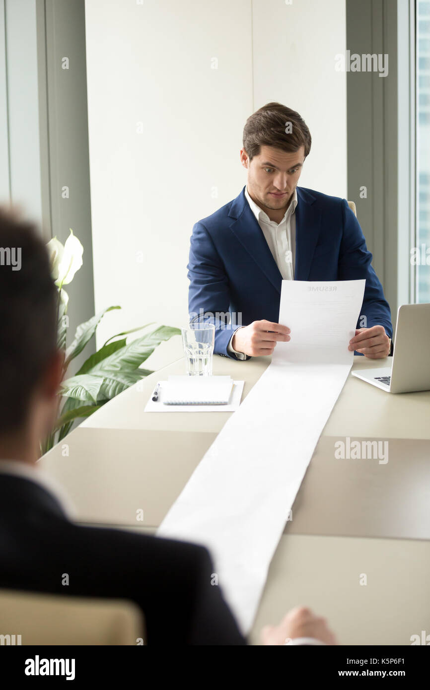 HR manager reading too long candidates resume - Stock Image