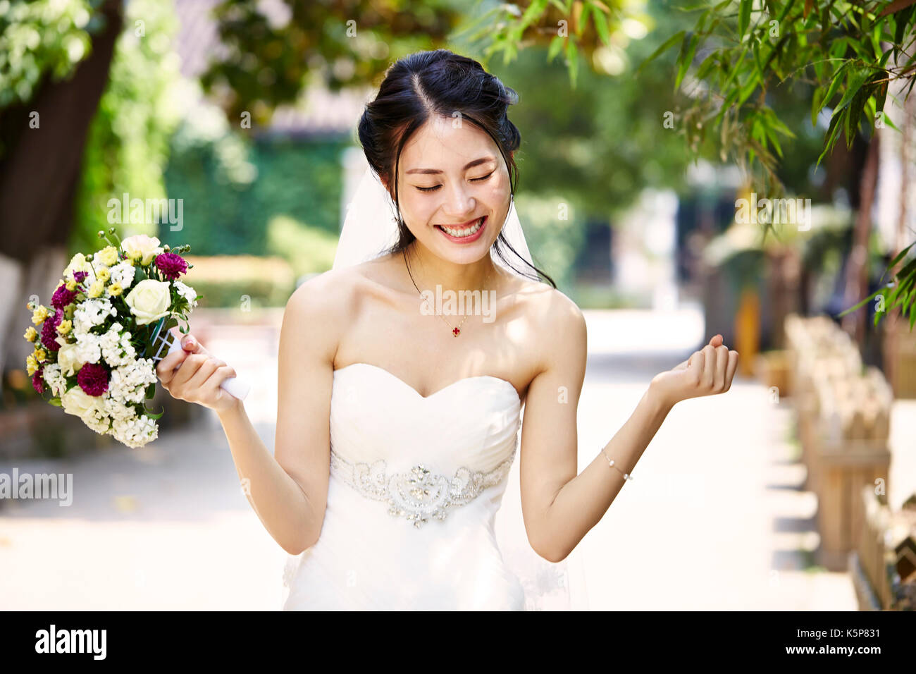 young and beautiful asian bride rejoicing with bouquet in hand. - Stock Image