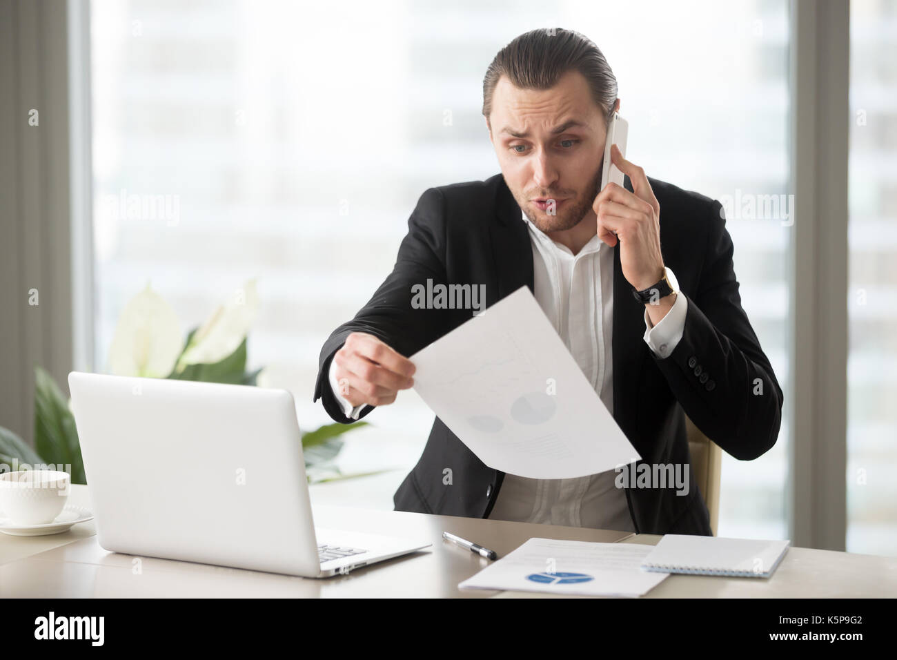 Shocked businessman talks on the phone holding financial report  - Stock Image