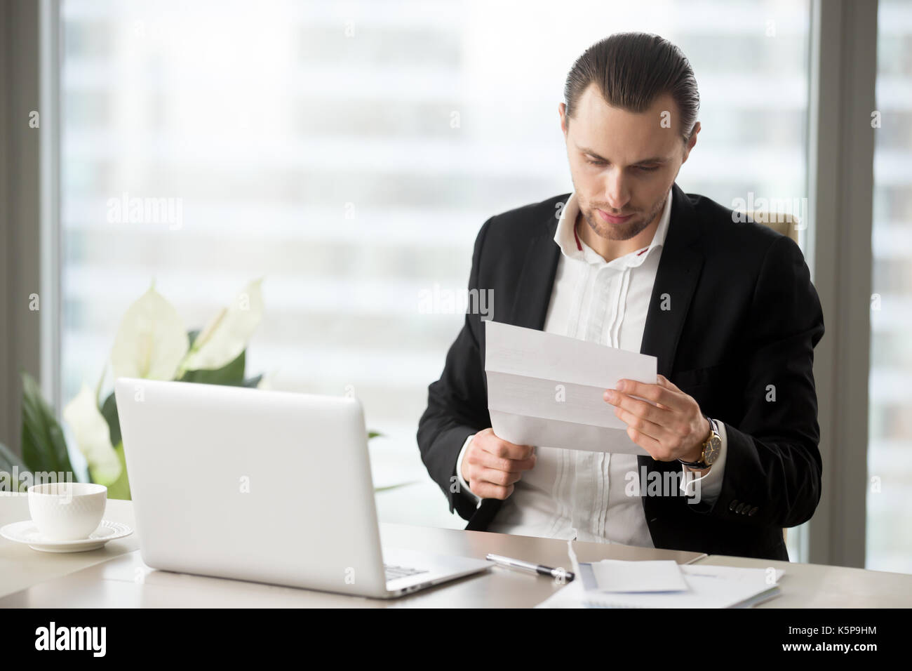 Young businessman in the office reading important financial lett - Stock Image