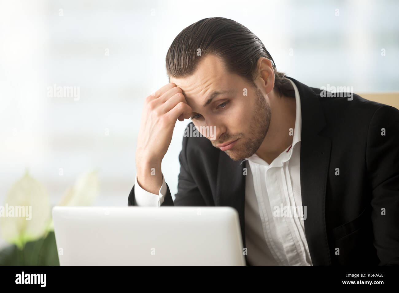 Puzzled young businessman looking at laptop screen at workplace. - Stock Image