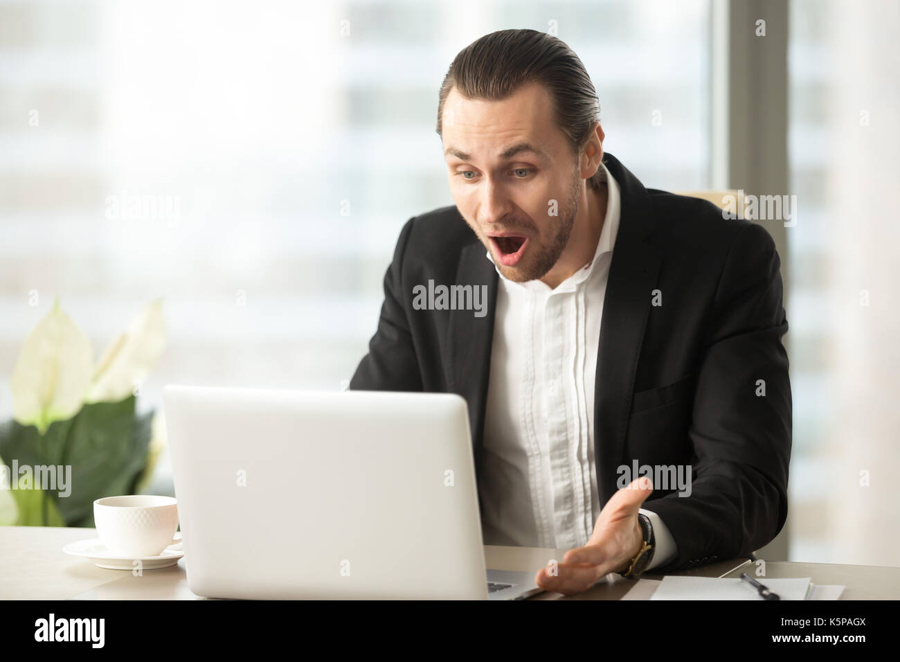 Frustrated young businessman looks at laptop screen screaming in - Stock Image