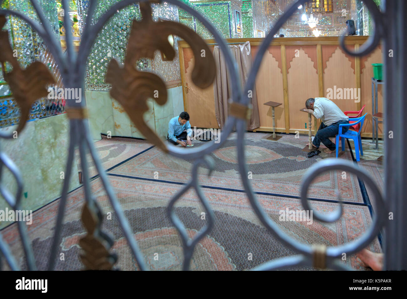 Fars Province, Shiraz, Iran - 18 april, 2017:  Muslim Shiite Men praying inside mirrored  Mosque of Sayyed Alaeddin Hossein. - Stock Image