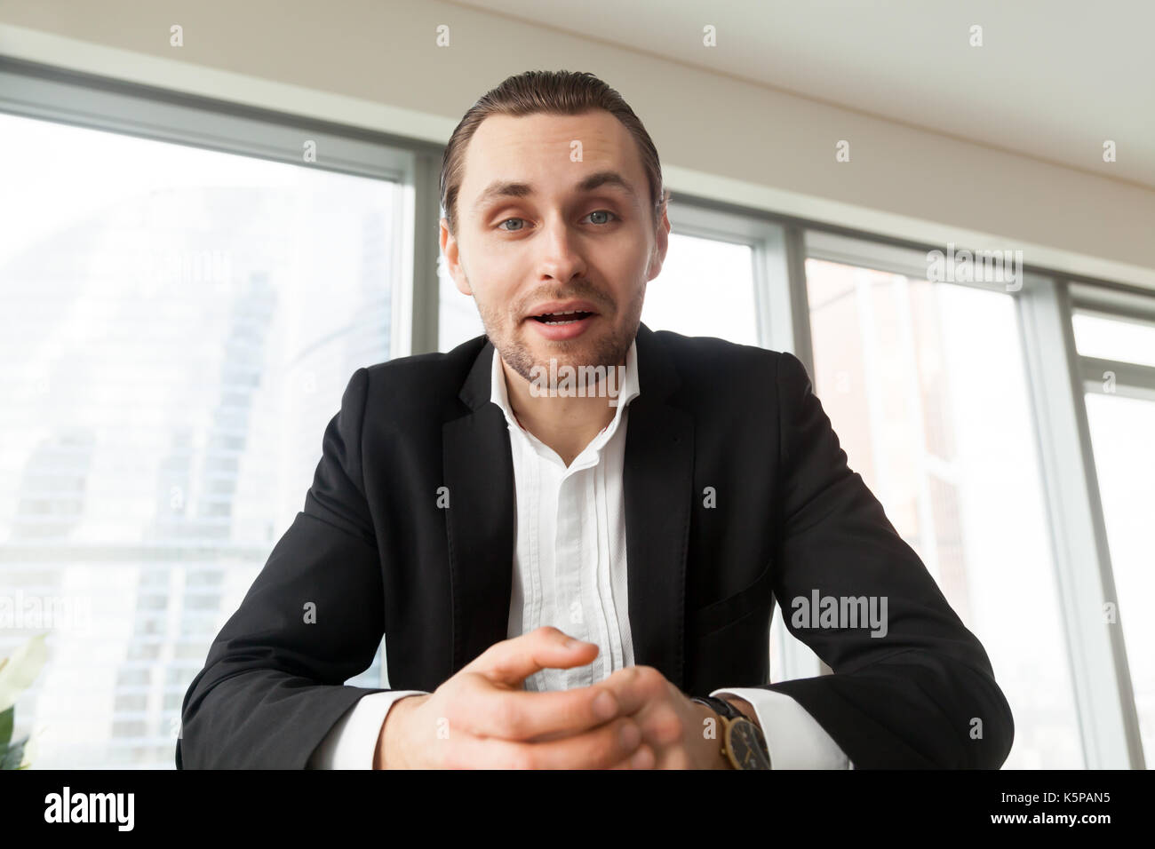 Portrait of young businessman looking in camera and talking. - Stock Image