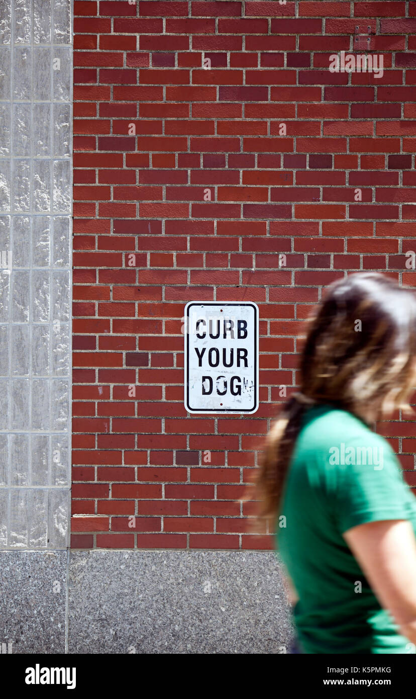 Curb Your Dog Sign with Pedestrian  in New York, USA - Stock Image