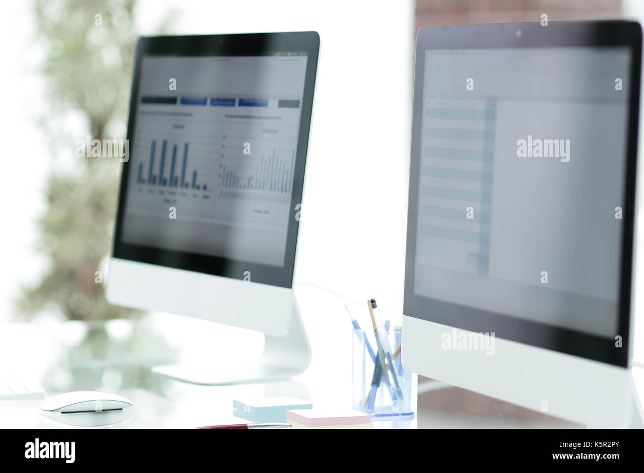 close-up of the screens of personal computers on a modern workplace in the office. - Stock Image