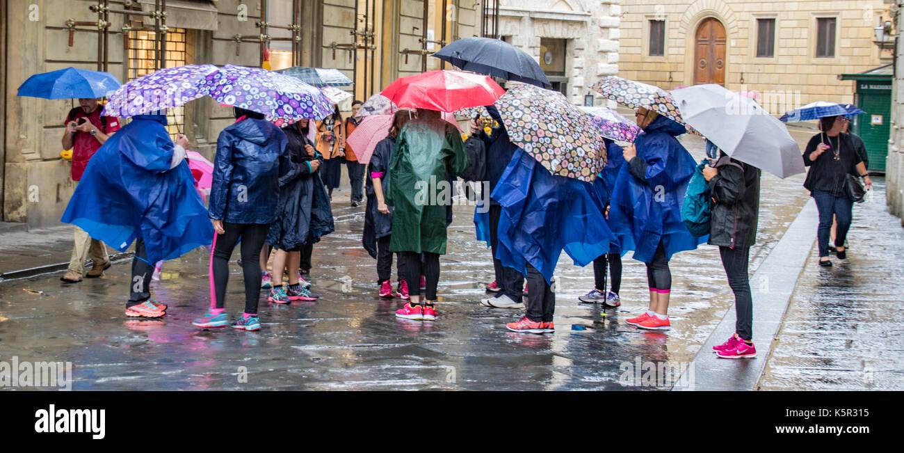 Tuscany, Italy - May 6, 2017: People huddle with rain ponchos and umbrellas Stock Photo