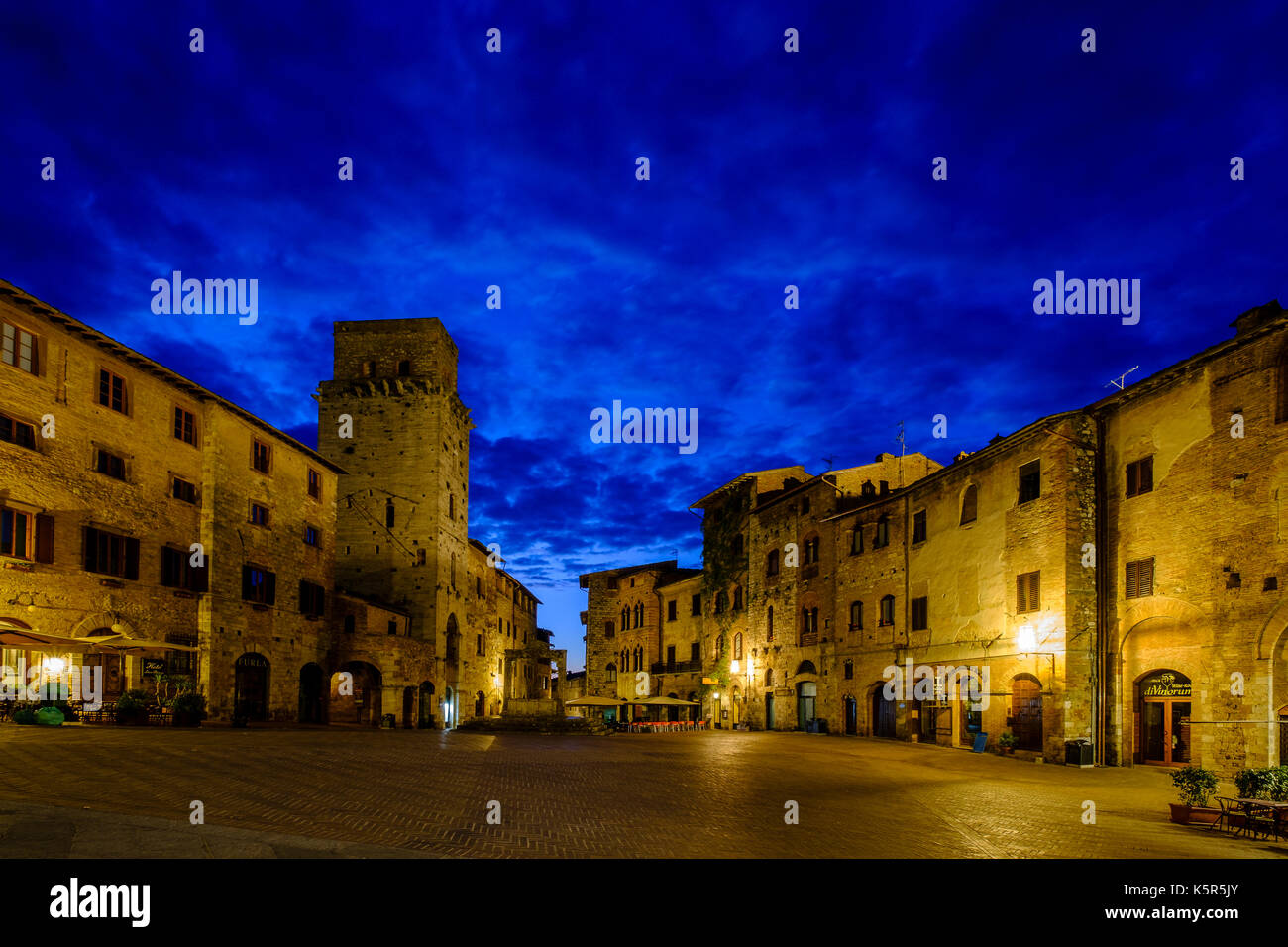 Old houses encircle the Piazza della Cisterna in the middle of the medieval town, illuminated at night - Stock Image