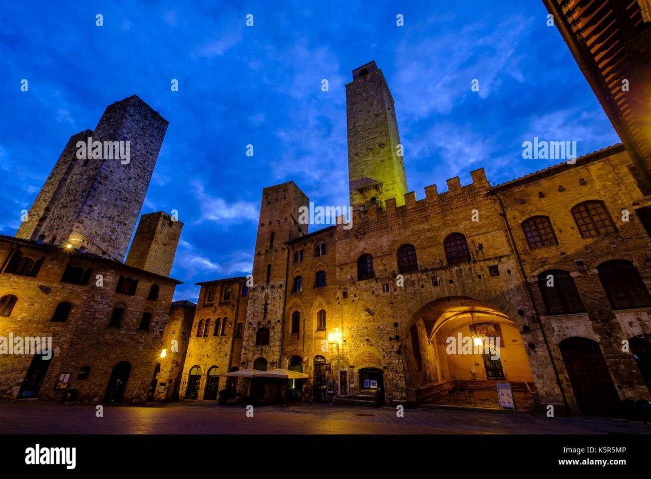 Old towers encircle the Piazza Duomo in the middle of the medieval town, illuminated at night - Stock Image