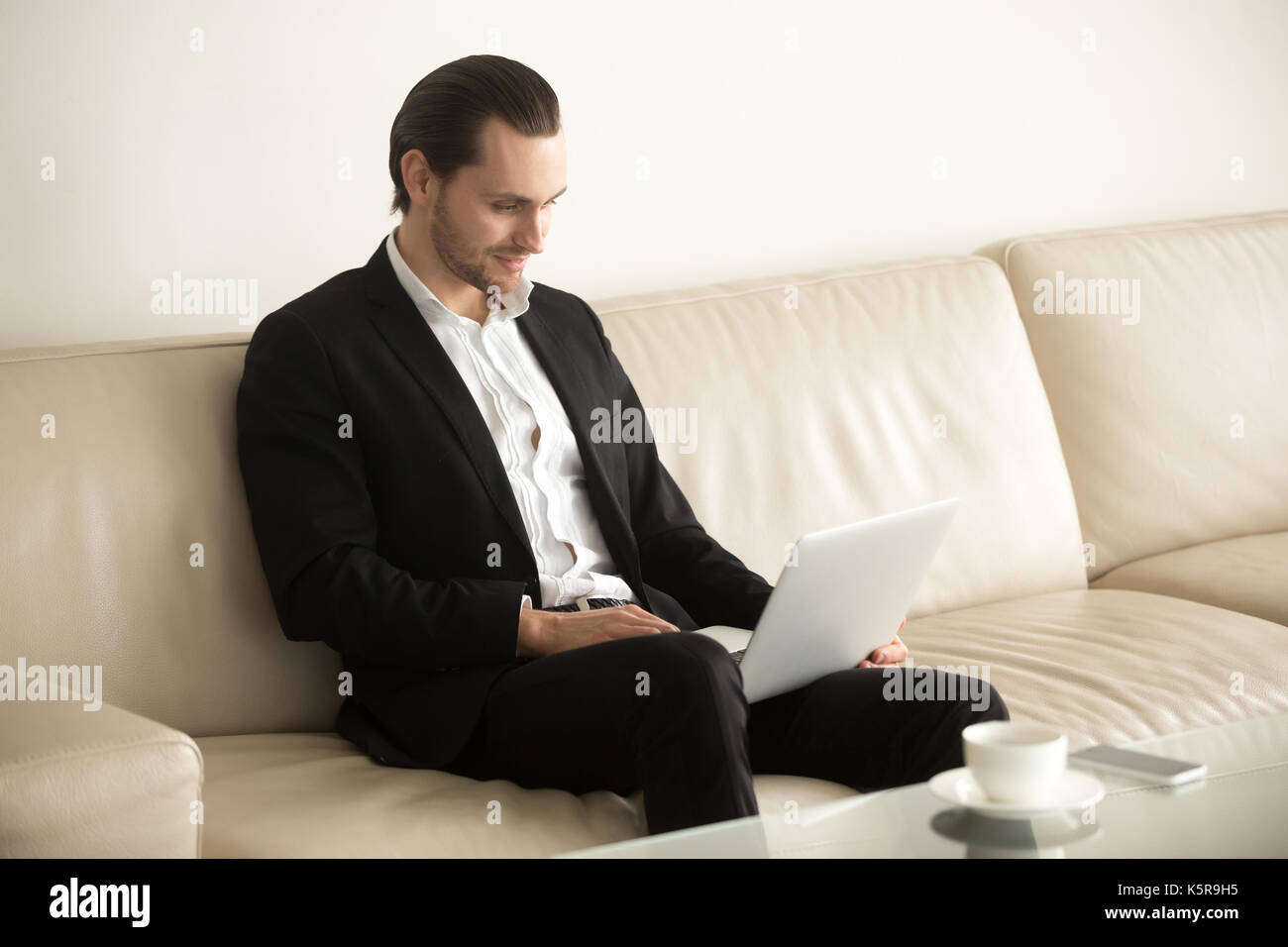 Smiling businessman working on laptop remotely from home. - Stock Image