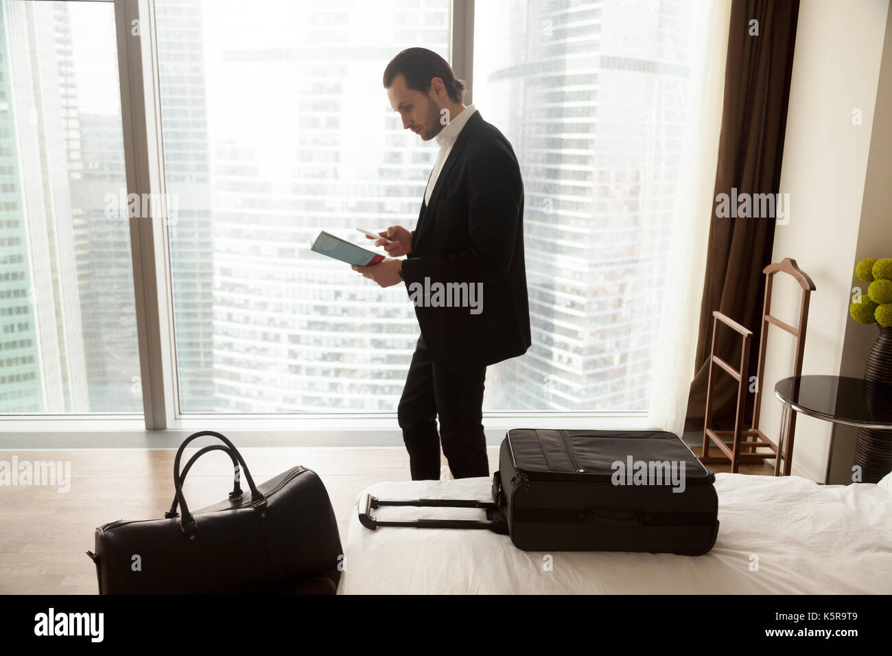 Businessman holds guide brochure and calls taxi or room service. - Stock Image