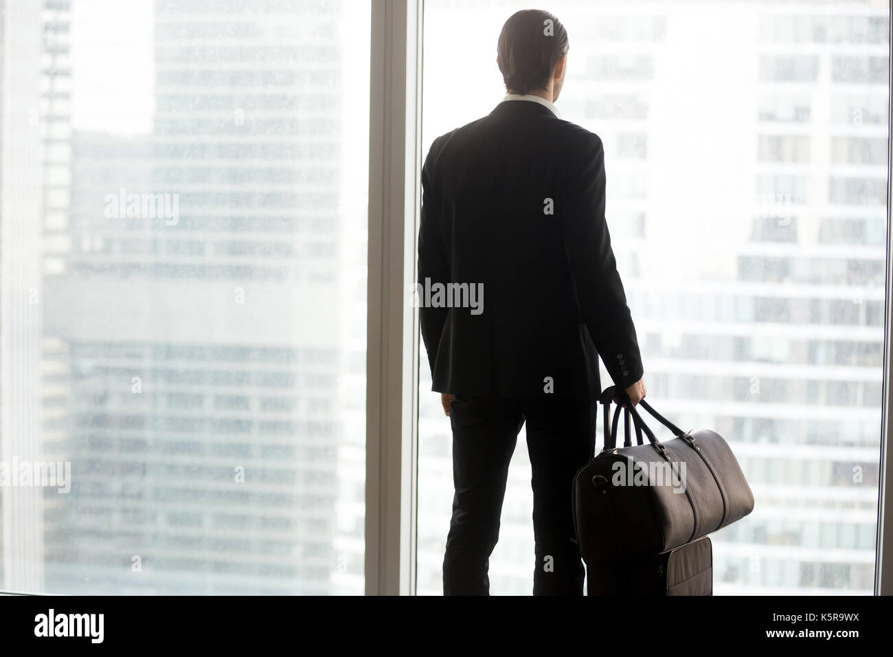 Businessman with luggage standing in front of large window. - Stock Image