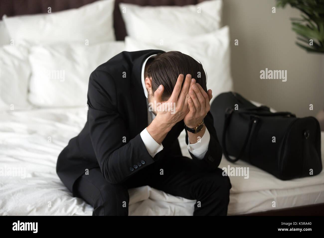 Stressed upset businessman sitting on bed, having headache. - Stock Image