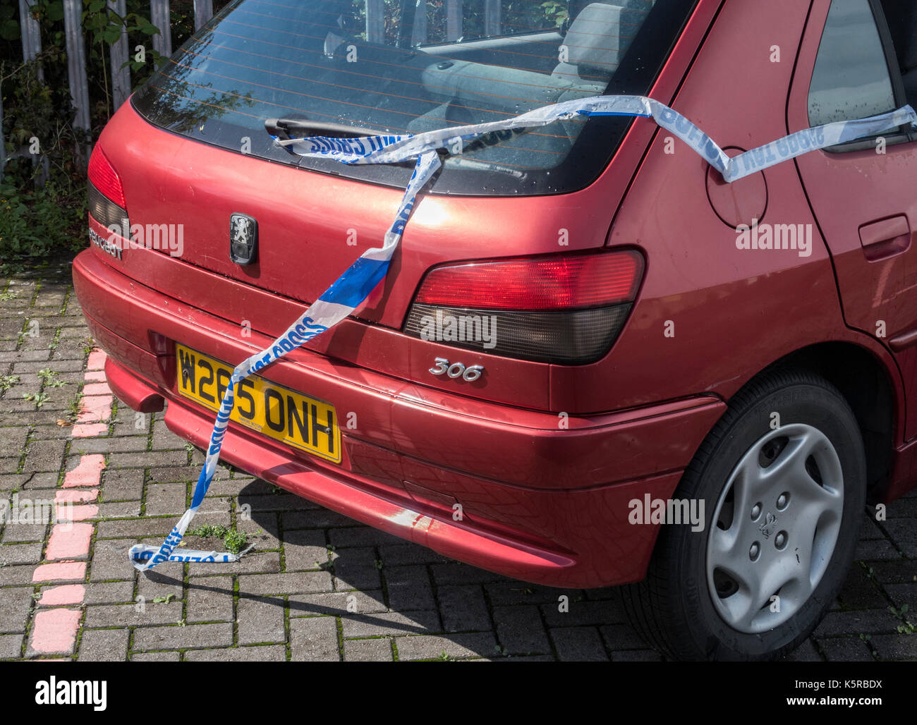 Abandoned and vandalised car - Peugeot 306, tied with 'Police Do Not Cross Tape' at Cullompton services on the M5 - Stock Image