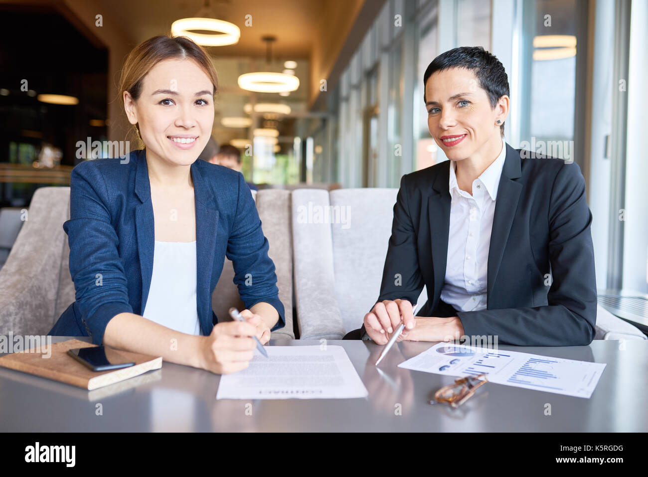 Cheerful business partners posing for photography with toothy smiles while having productive meeting at modern restaurant - Stock Image