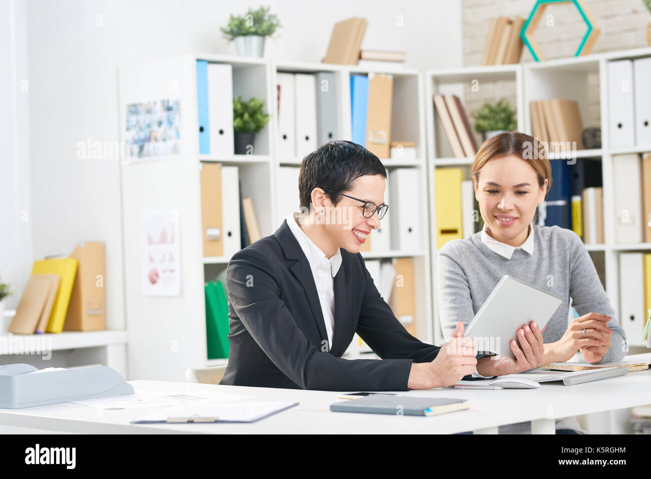 Joyful managers in formalwear gathered together at modern open plan office and making presentation with help of digital tablet - Stock Image