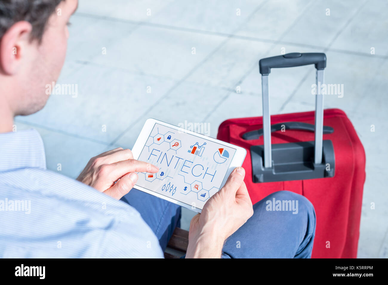 Businessman at airport using digital tablet computer with infographic concept of fintech (financial technology) on the screen, business travel - Stock Image