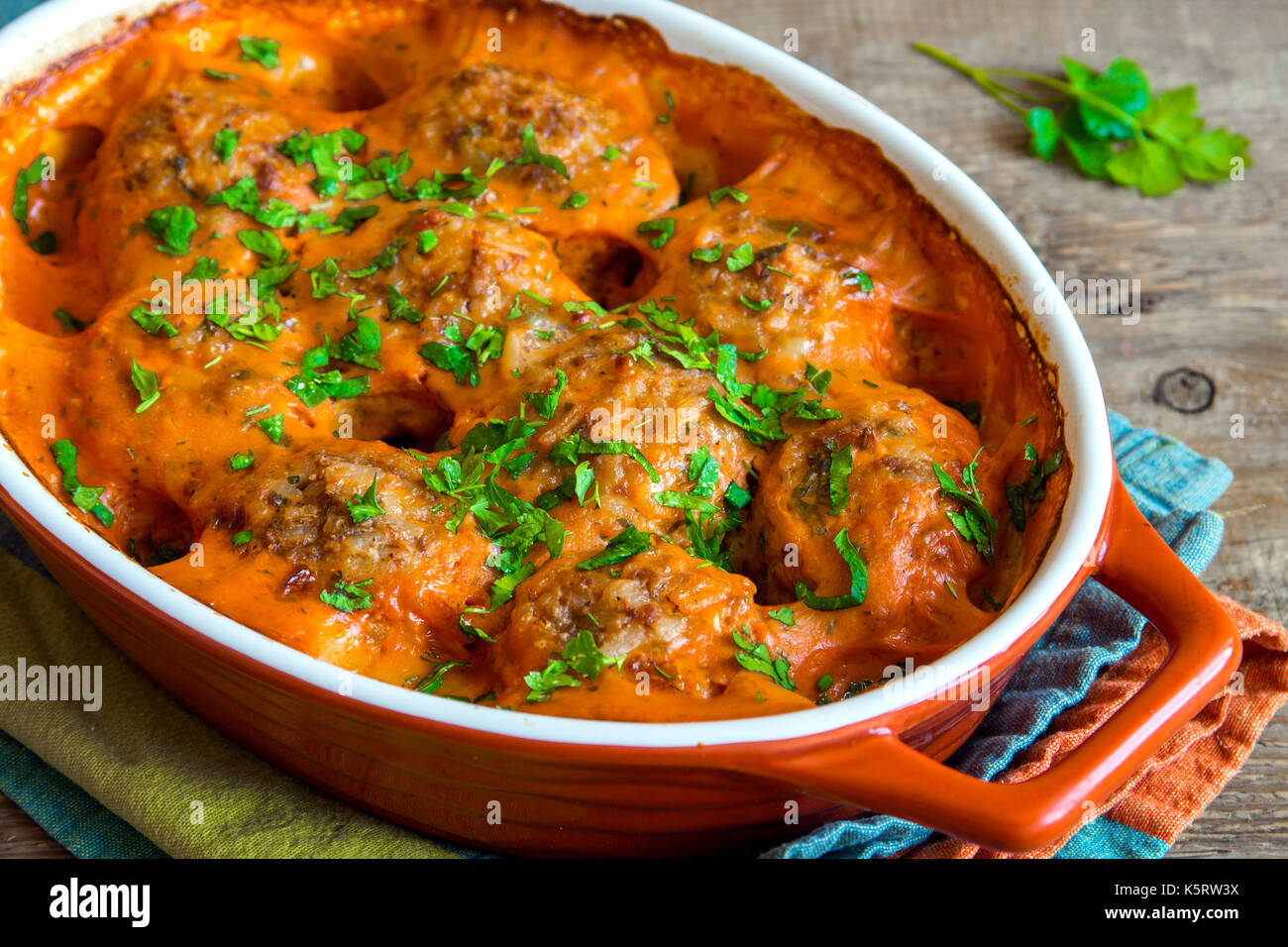 Baked meatballs with tomato sauce and parsley in baking dish over rustic wooden background - Stock Image