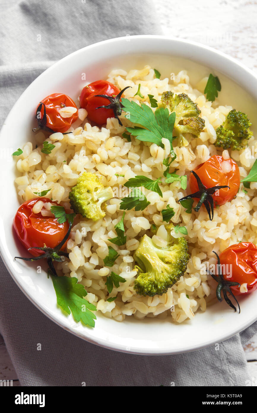 Bulgur with vegetables: tomatoes, carrots, zucchini, broccoli and parsley in rustic wooden bowl - healthy vegetarian food - Stock Image