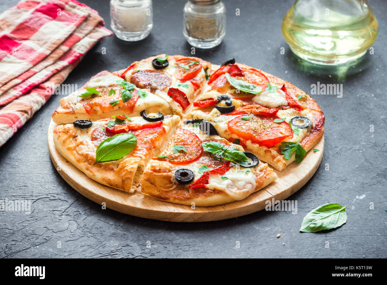 Italian Pizza with Tomatoes, Salami, black Olives and Mozzarella Cheese, top view. Fresh Homemade Pizza. - Stock Image