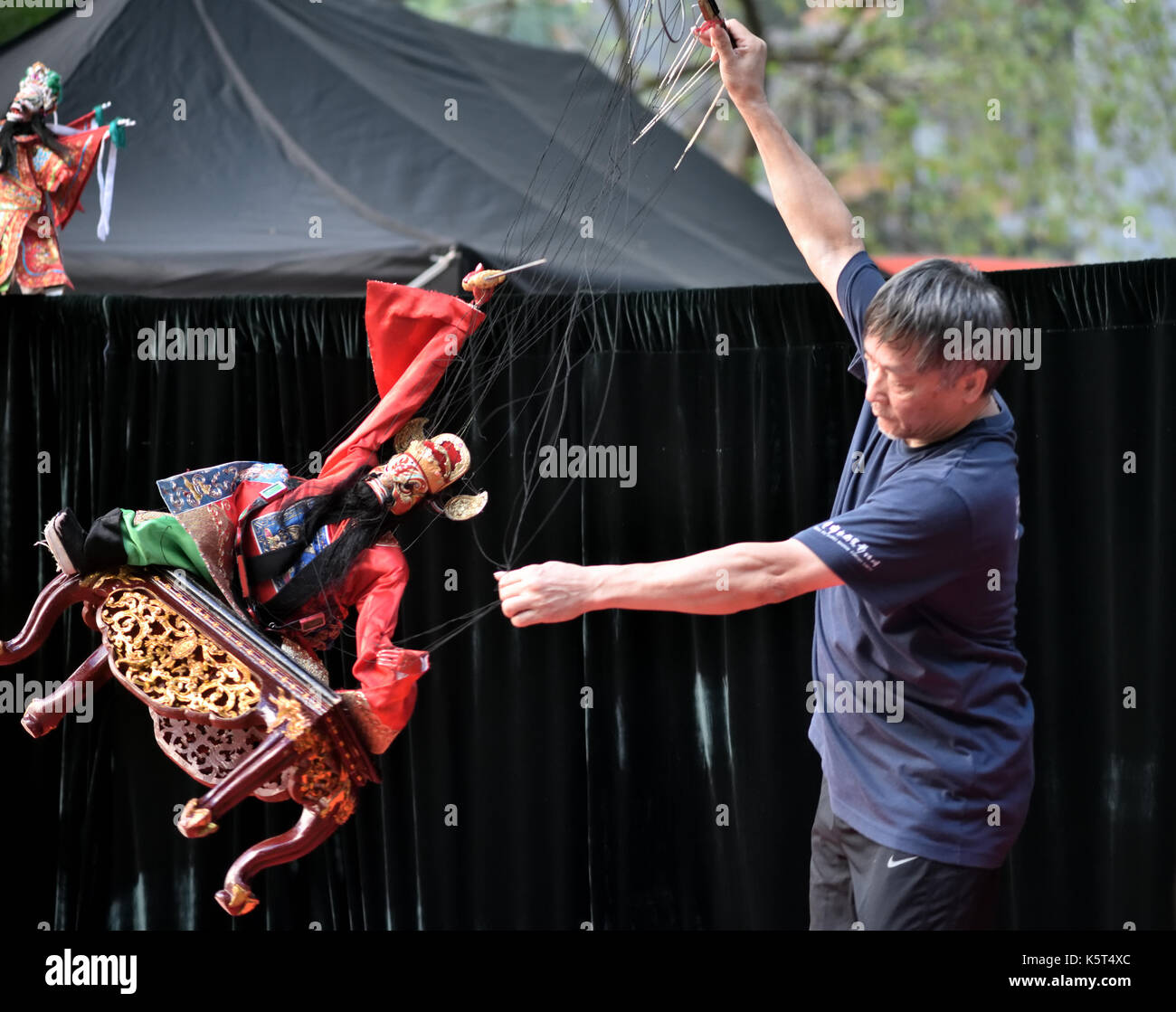 Traditional Chinese string puppet show performed outdoor for  public entertainment. - Stock Image