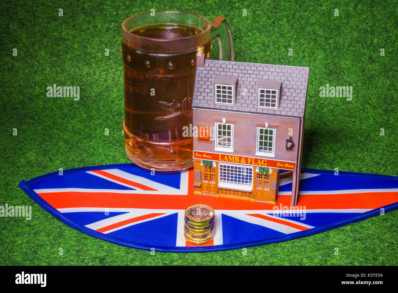 Model British pub with drink and a Union Jack with new pound coins. UK drinks industry concept, with costs from business and customer perspectives. - Stock Image