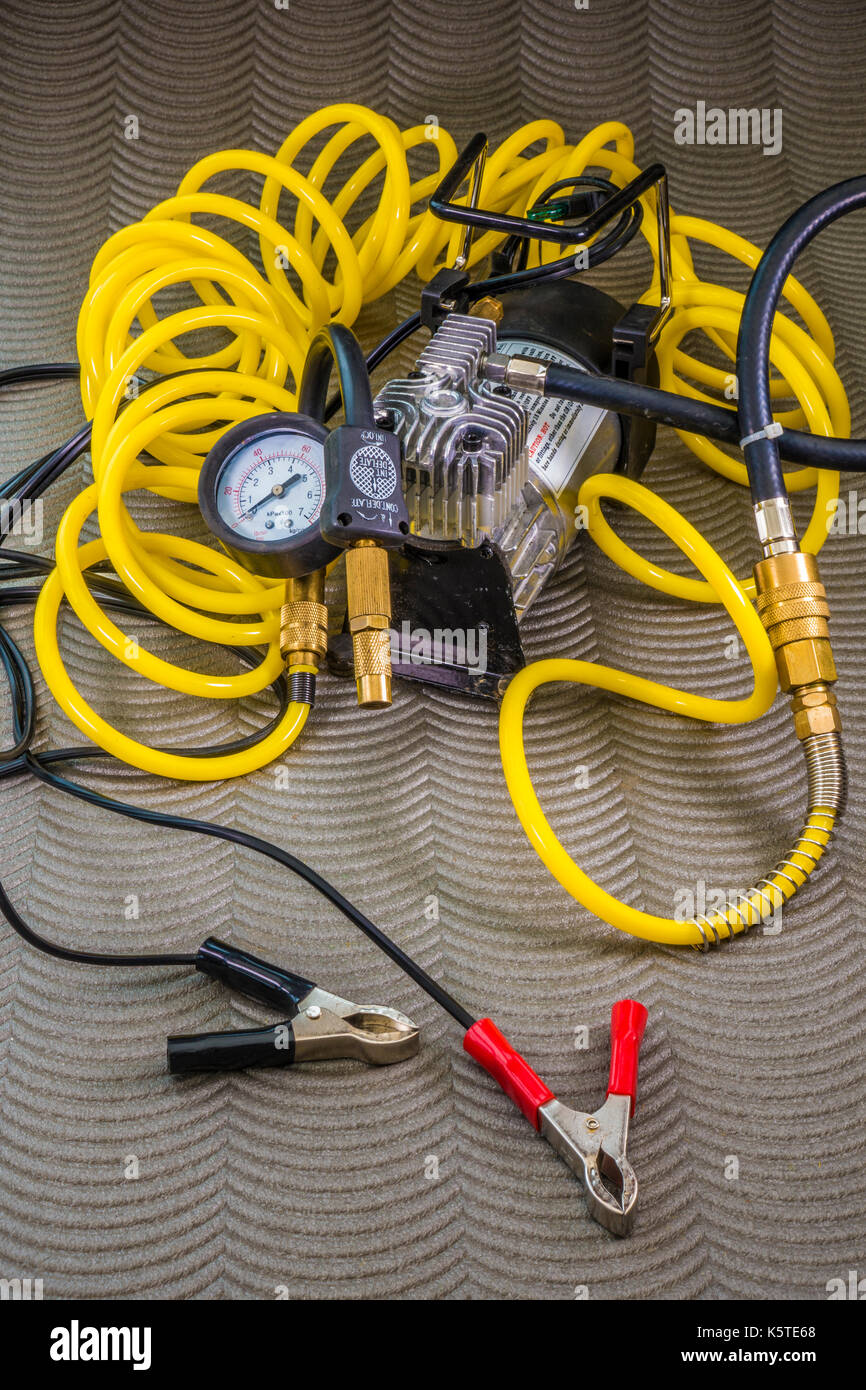 12 volt professional tyre inflator, with compressor, brass fittings, long coiled air hose and crocodile clips for connection to battery terminals. - Stock Image