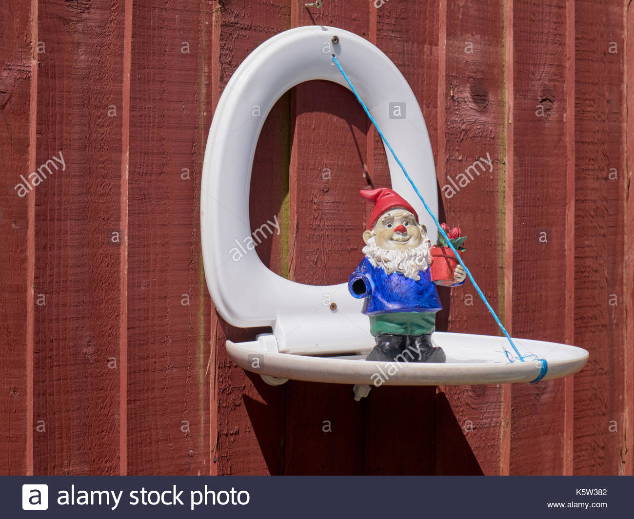 A white plastic toilet seat reused as a garden ornament fixed to a brown wooden fencing panel with a garden gnome in the uk - Stock Image