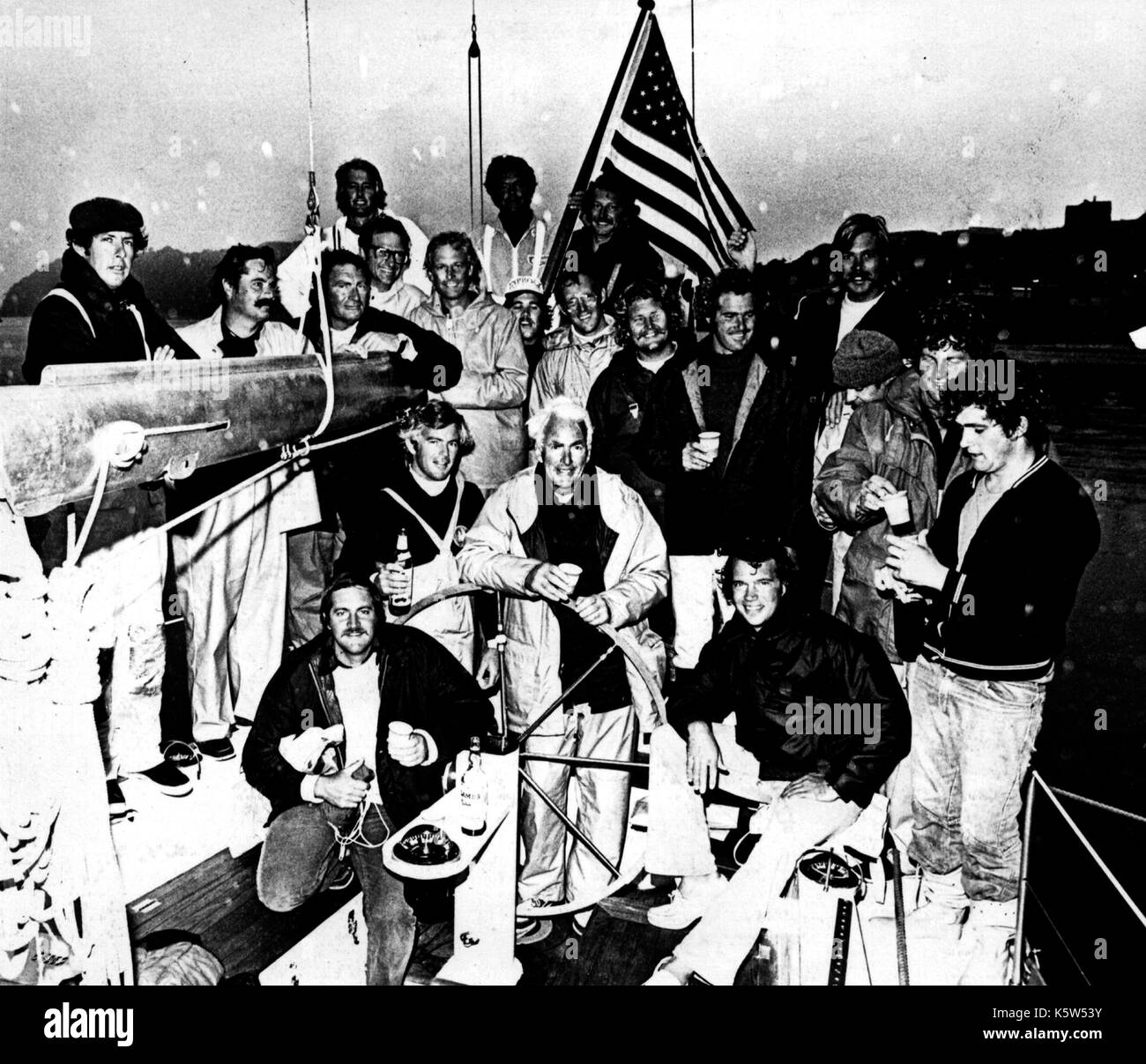 AJAXNETPHOTO. 13TH AUGUST, 1975. PLYMOUTH, ENGLAND. - FASTNET RACE - SKIPPER AND OWNER JIM KILROY OF LOS ANGELES (CENTRE, BEHIND WHEEL) AND THE 20 MAN CREW OF THE AMERICAN YACHT KIALOA ON ARRIVAL AFTER IT TOOK LINE HONOURS AT THE END OF THE 605 MILE RACE. 