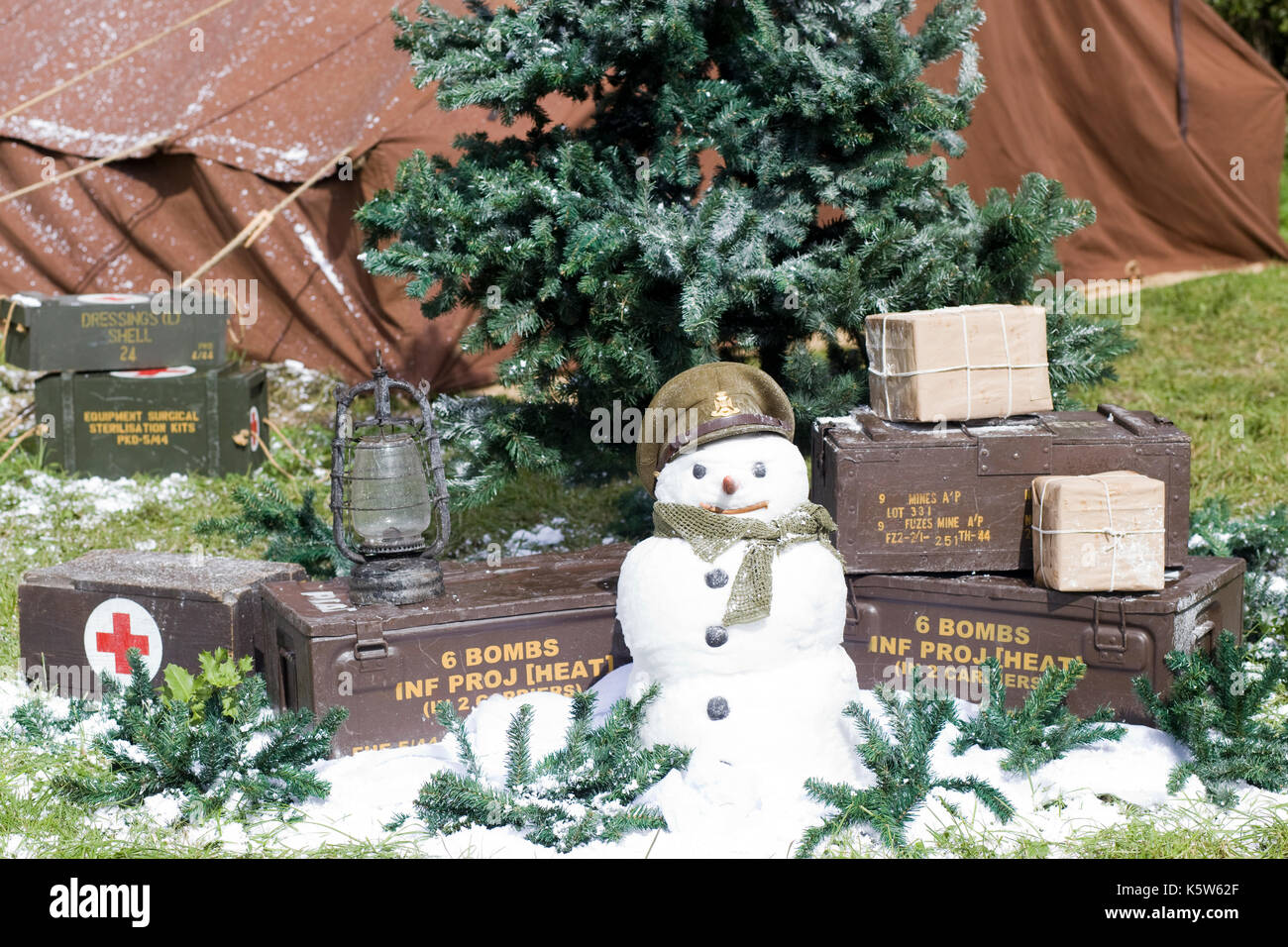 christmastime in the trenches snowman and christmas tree surrounded by ammunition stock image - Christmas Bombings