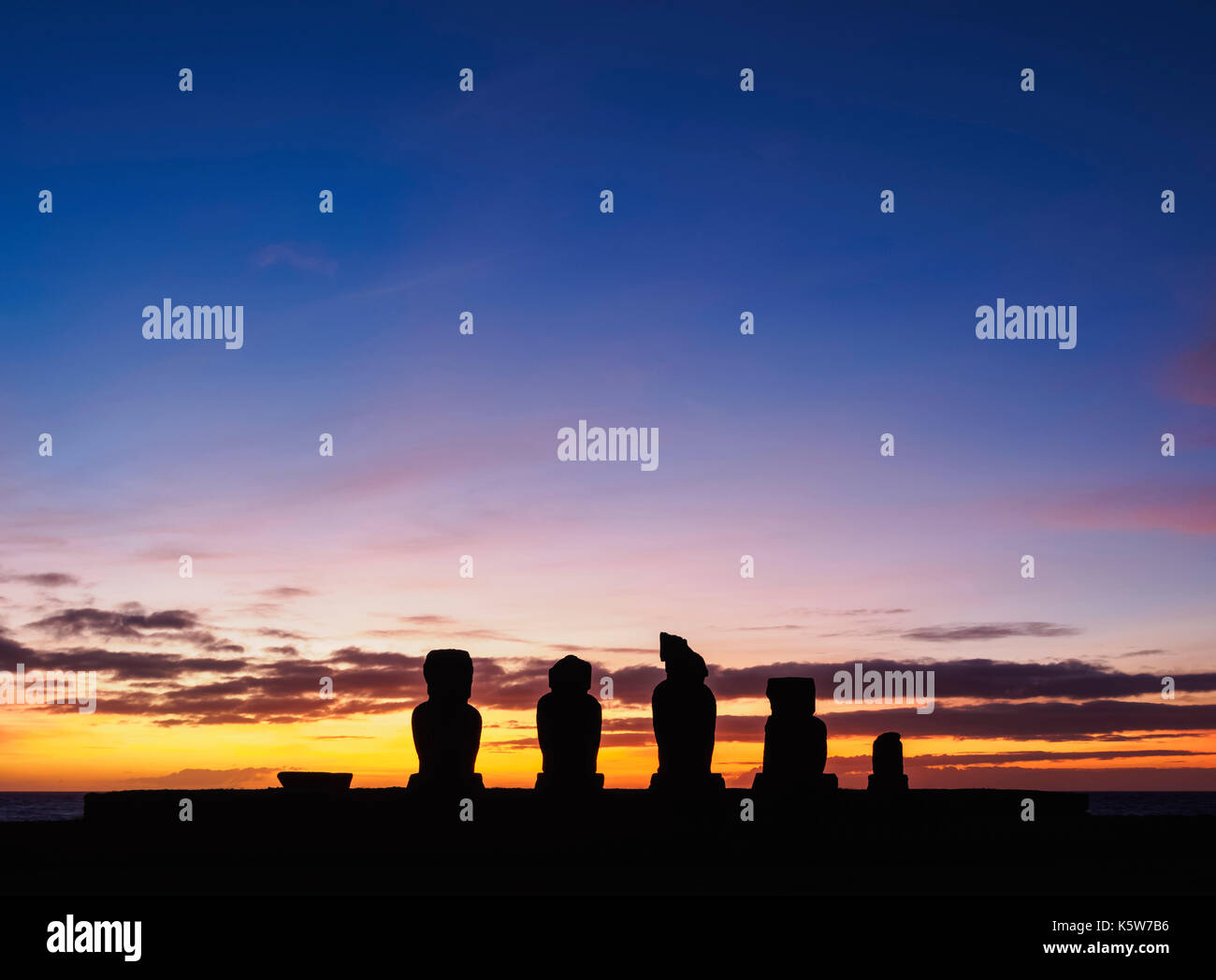 Moais in Ahu Vai Uri at sunset, Tahai Archaeological Complex, Rapa Nui National Park, Easter Island, Chile - Stock Image