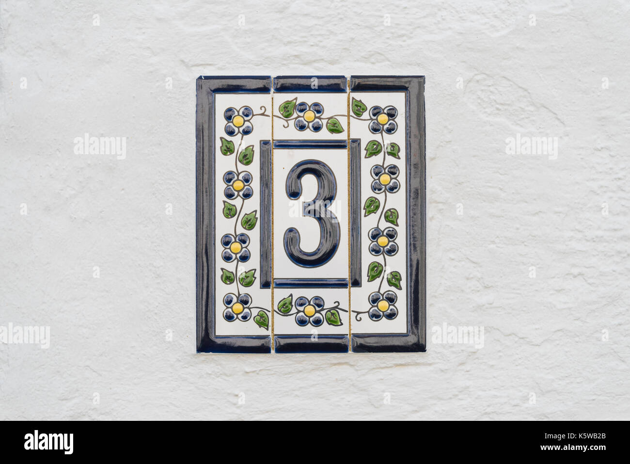 House Number Three Decorated With Tiles On A White Wall