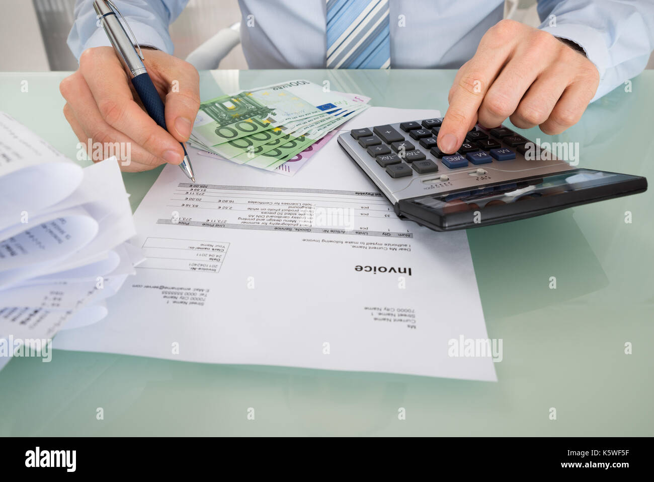 Close-up Of A Businessman Calculating Invoice With Euro Banknotes At Desk Stock Photo
