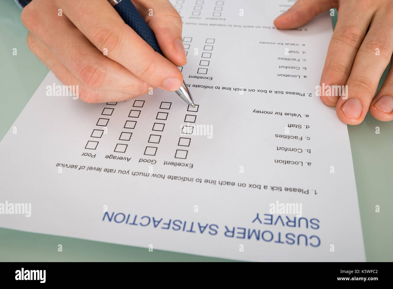 Close-up Of Person Hand Filling Customer Satisfaction Form - Stock Image