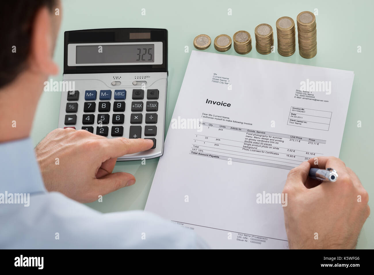 Close-up Of Businessperson Calculating Invoice With Coins At Desk Stock Photo