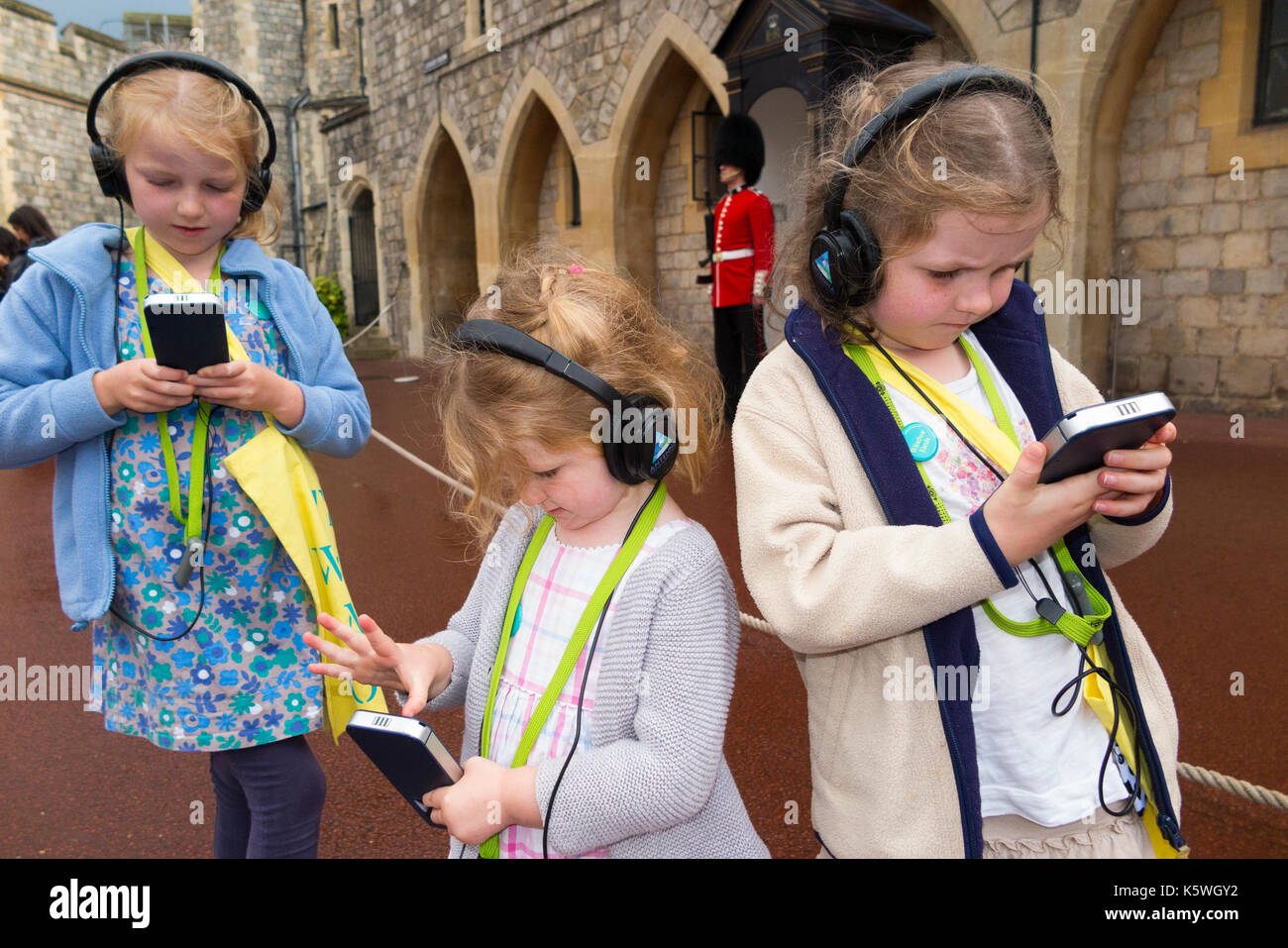 Three sisters /children /kid /kids on holiday listen to an audio guide information while on a tour inside the walls of Windsor Castle, Berkshire UK. - Stock Image