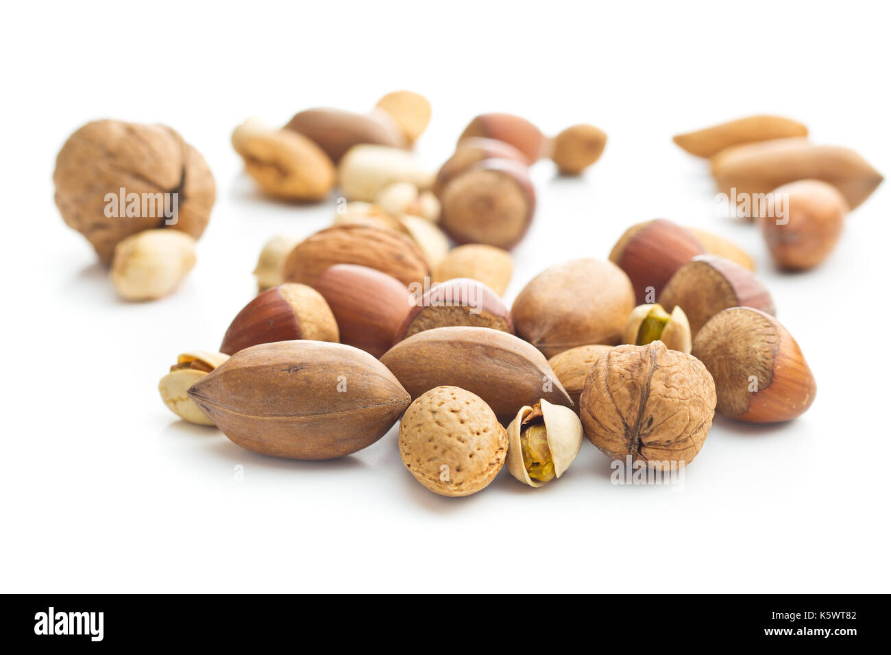 Different types of nuts in the nutshell. Hazelnuts, walnuts, almonds, pecan nuts and pistachio nuts isolated on white background. - Stock Image