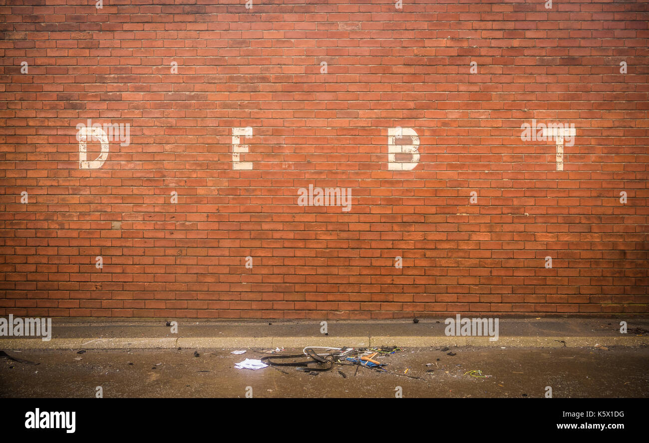 Grungy Red Brick Wall With The Word Debt - Stock Image
