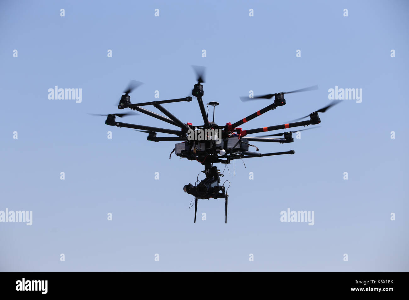 Black hexacopter octocopter is flying in sky - Stock Image