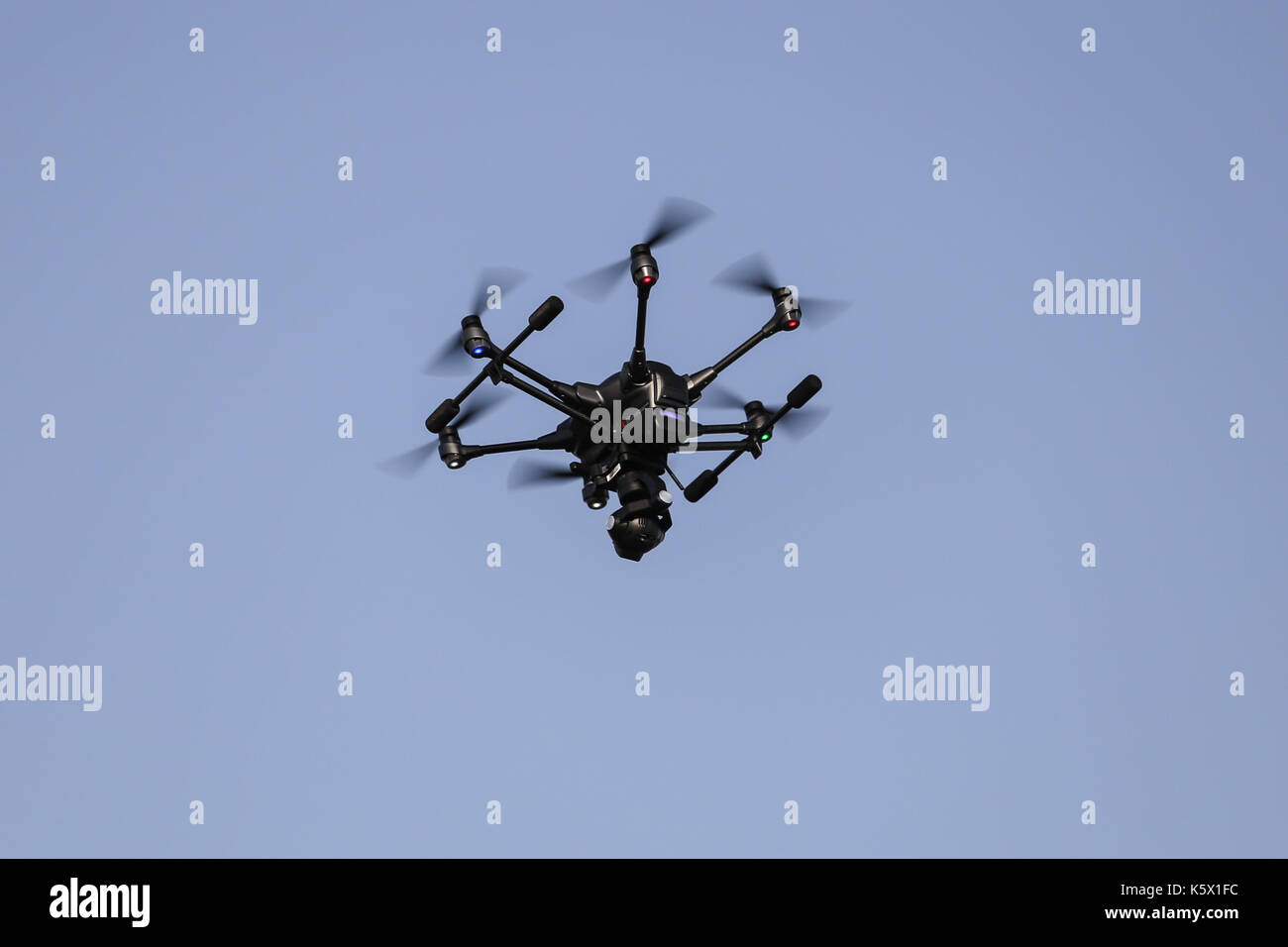 Black hexacopter helicopter is flying in sky - Stock Image