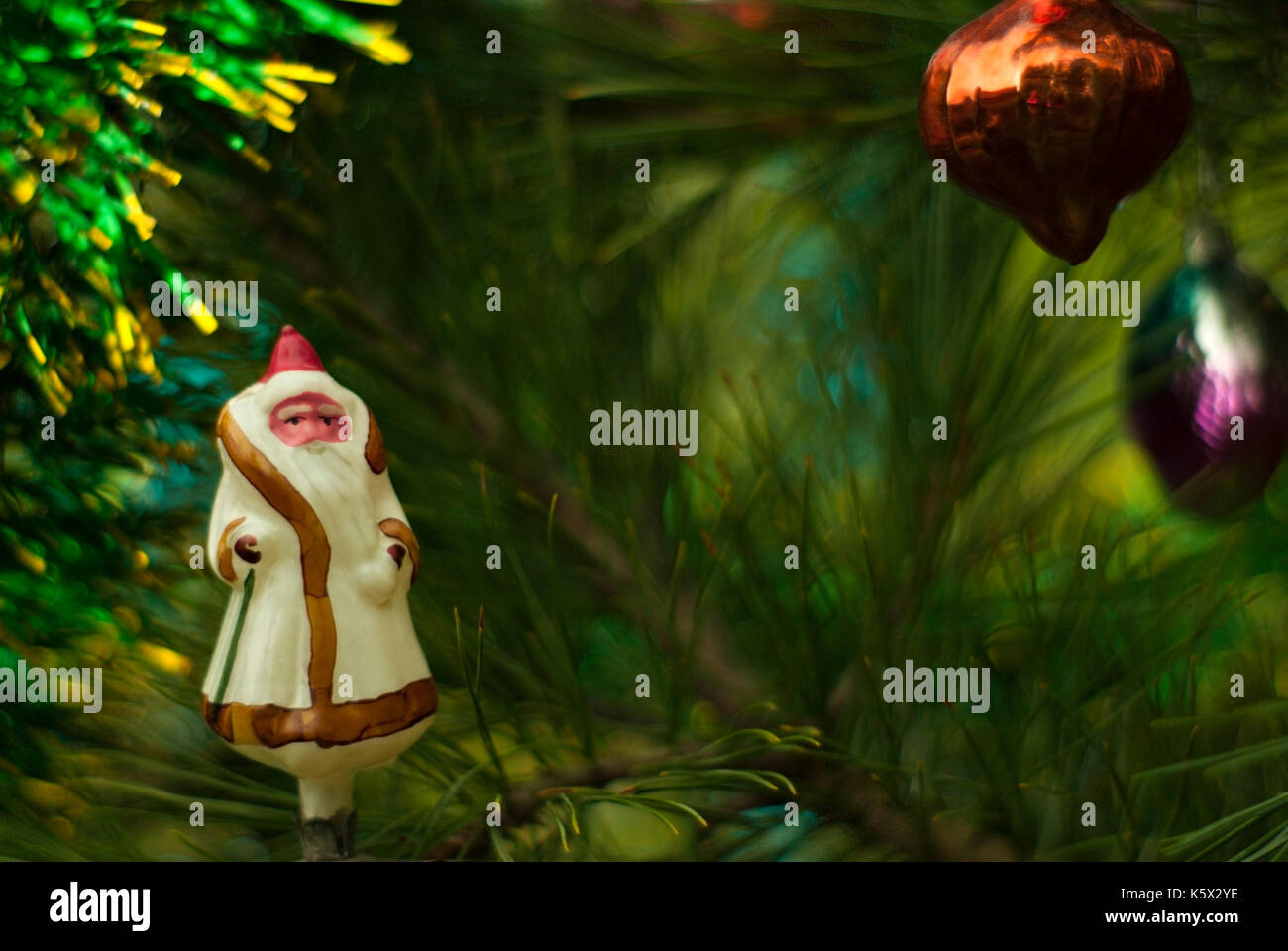 Vintage glass Christmas tree toy: Ded Moroz ('Grandfather Frost',slavic analog of Santa Claus) in the background of green branches. Blurred background - Stock Image