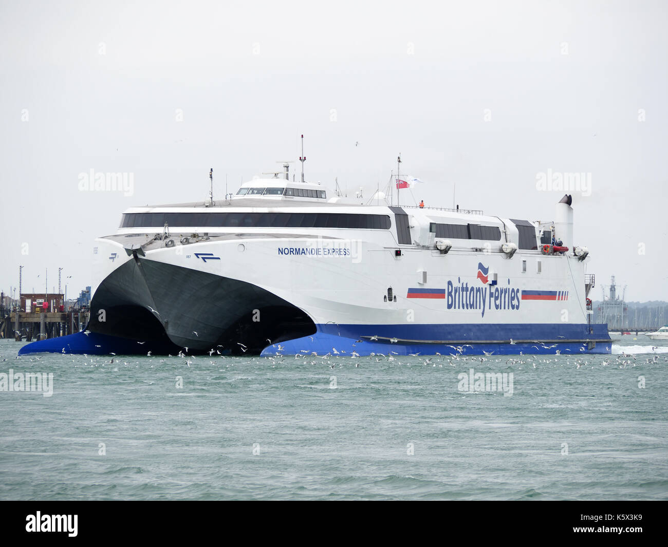 View of the Brittany Ferries Normandie Express high-speed catamaran departing from Portsmouth Harbour - Stock Image