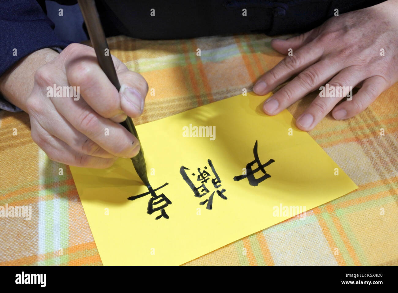 Taiwanese man writing Chinese calligraphy. Chinese calligraphy is a form of aesthetically pleasing writing. Chinese characters can be retraced to 4000 - Stock Image