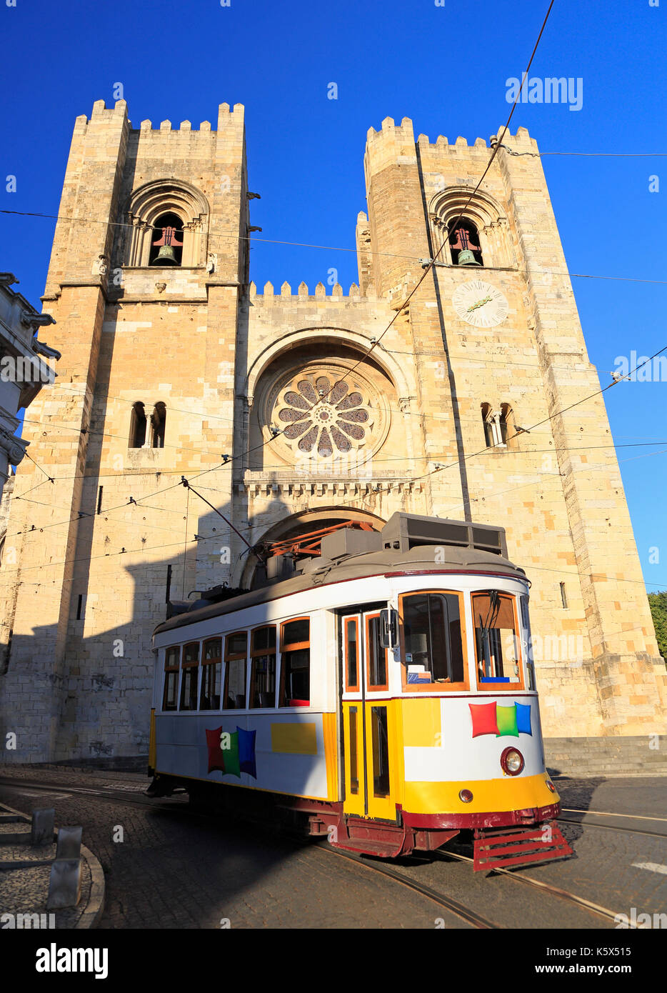 Famous yellow tram running in front of Se Cathedral in Lisbon, Portugal Stock Photo